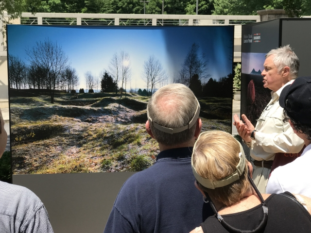 Man speaking to crowd in front of a picture of an old WW1 battlefield.  The battlefield has depressions in the ground from bombs but nature has taken over throughout the years.