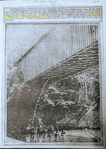 This photo was taken moments after the big army truck crashed through the bridge.  The bridge is a covered bridge and shows men down below in the water investigating the crashed truck.
