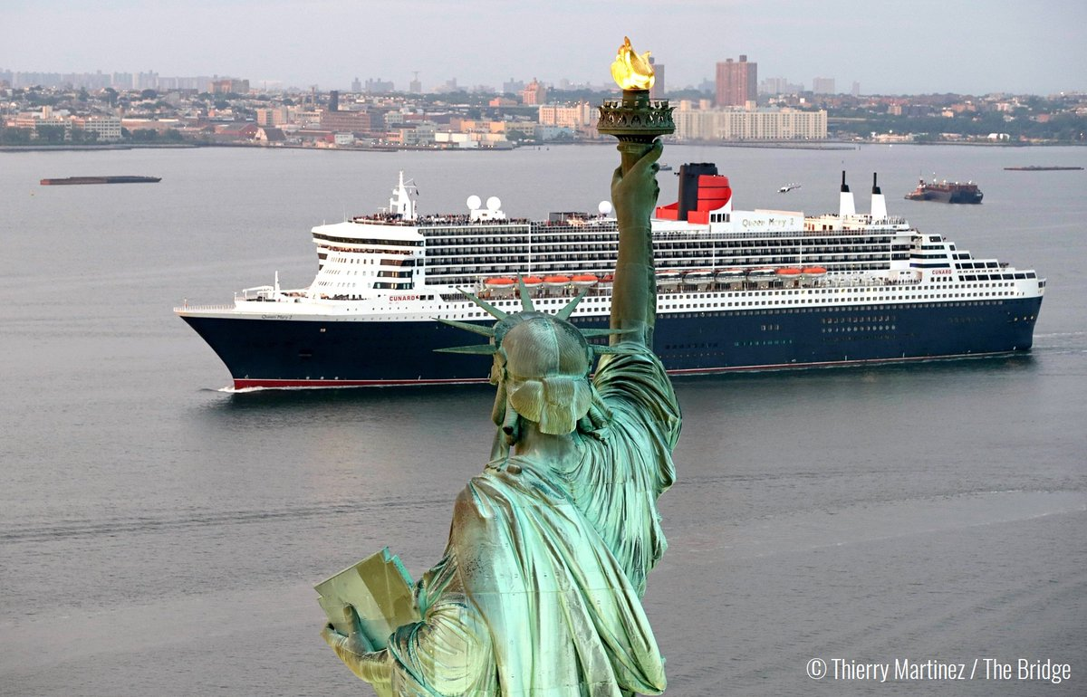 "Queen Mary II passes the Statue of Liberty in New York Harbor at the end of ""The Bridge"" race across the Atlantic from France."
