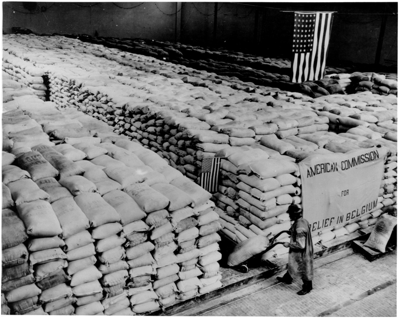 A warehouse in German occupied Belgium in WW1 with bags of flour for distribution under American supervision