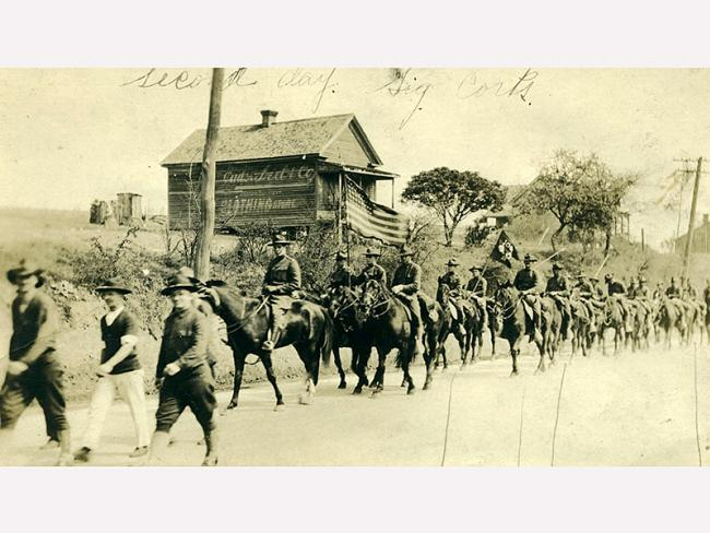 106th field signal battalion marching down a dirt road on horse back waving American flag