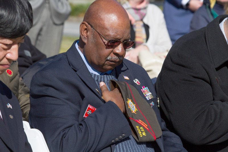 Charles A. Dobbins lowers his head throughout the invocation during the 2018 Veterans Day Commemoration