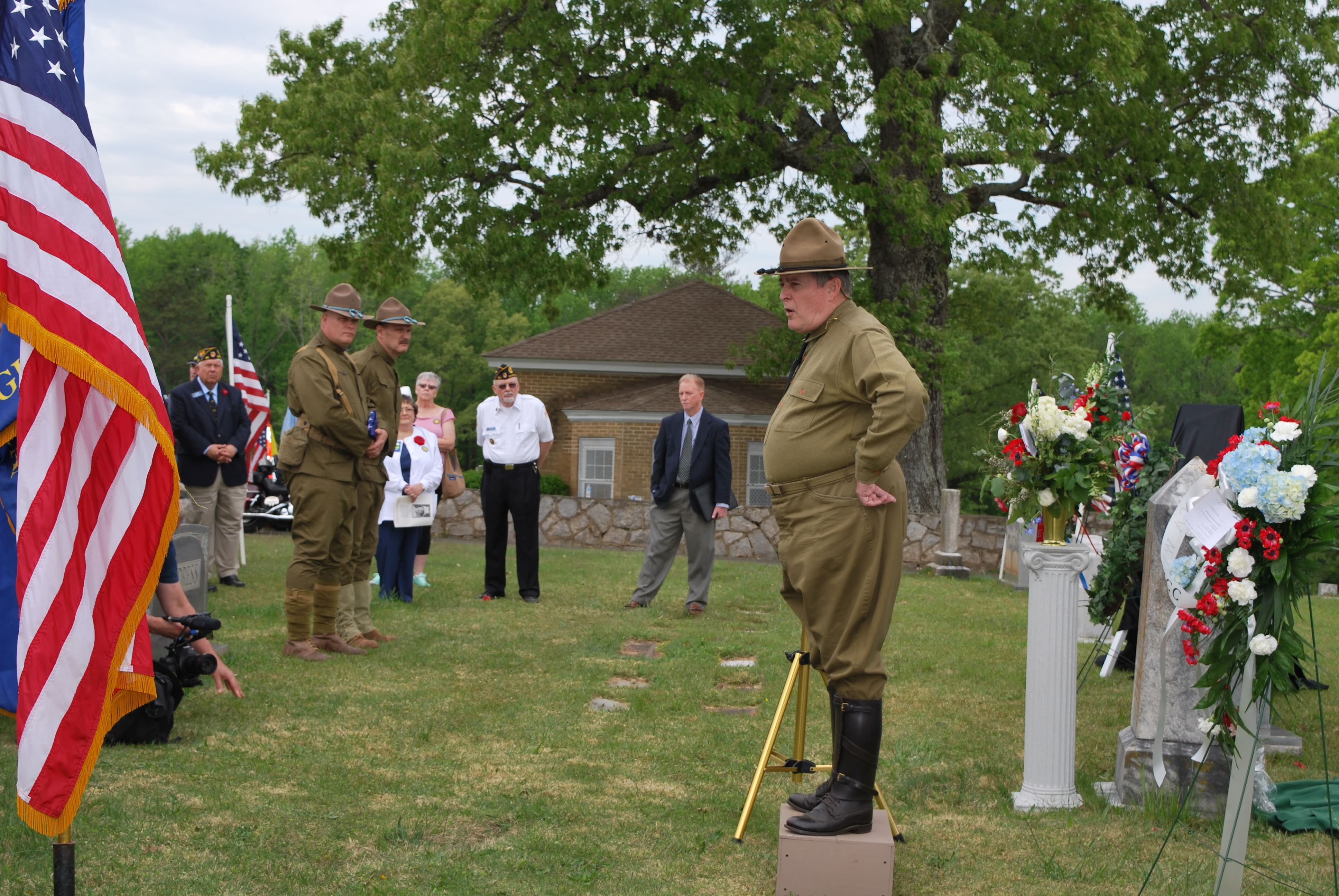 Soldier dressed in WW1 military attire stands atop a box and gives a speech