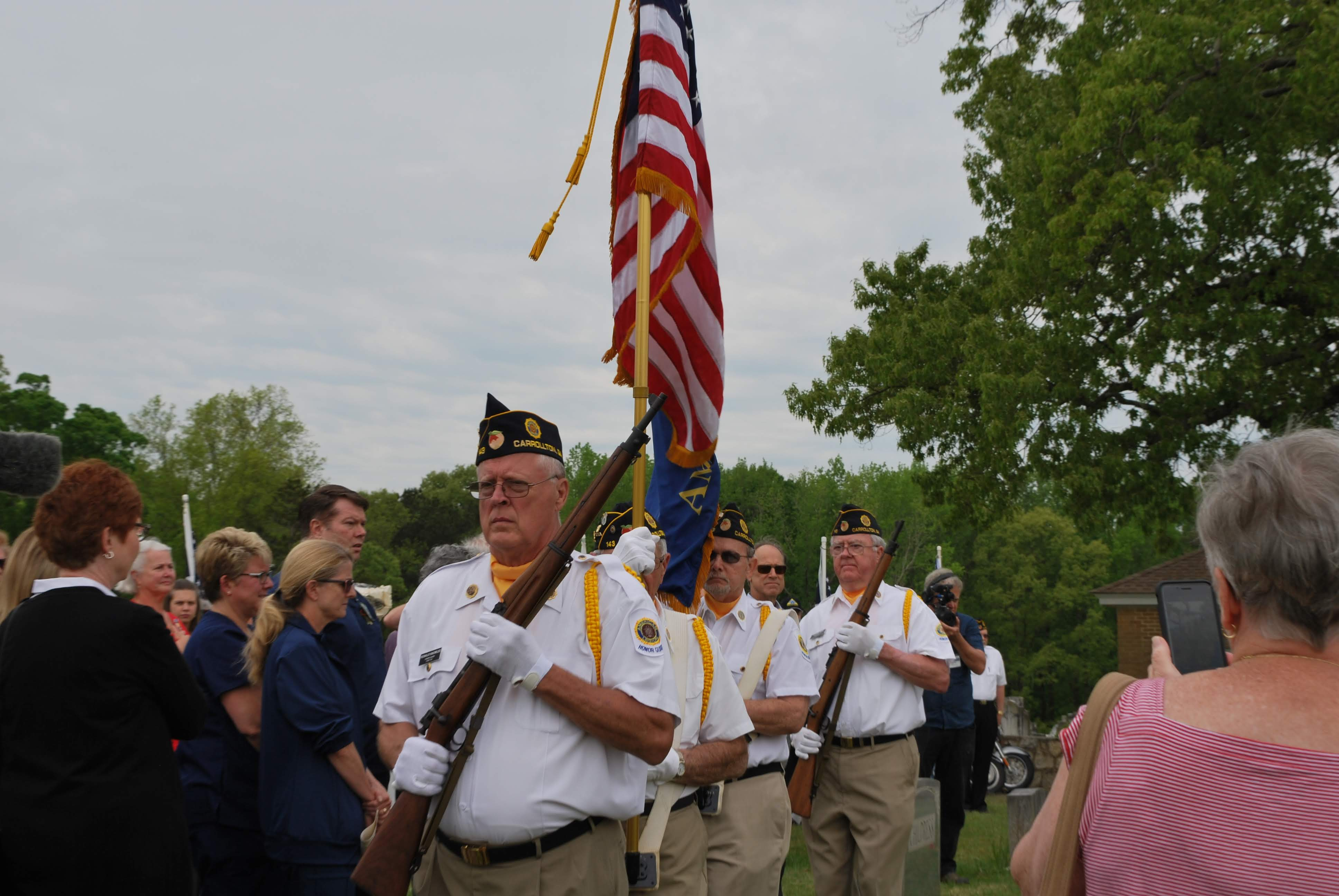 the color guard stand in a line with the US flag