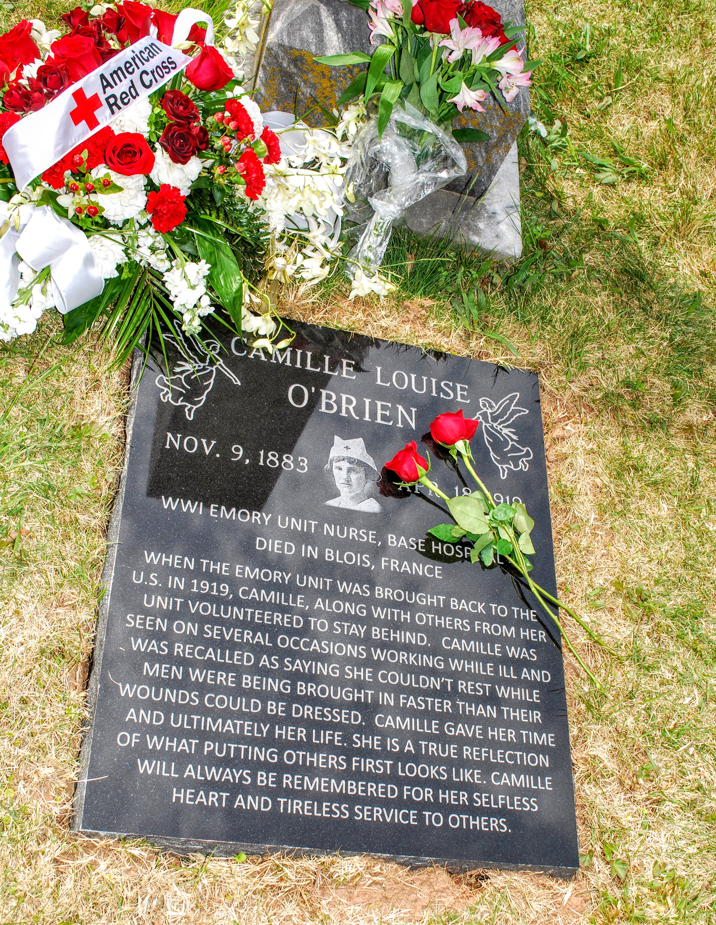 Grave marker for Camille O'Brien.  Two red roses lying on top