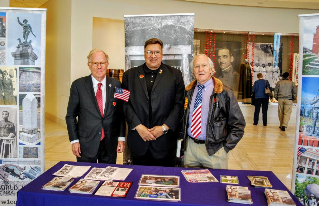 Three men stand behind a table with a purple table cloth. the table has pamphlets on it.  One man has an American flag tie and the other is holding a little American flag