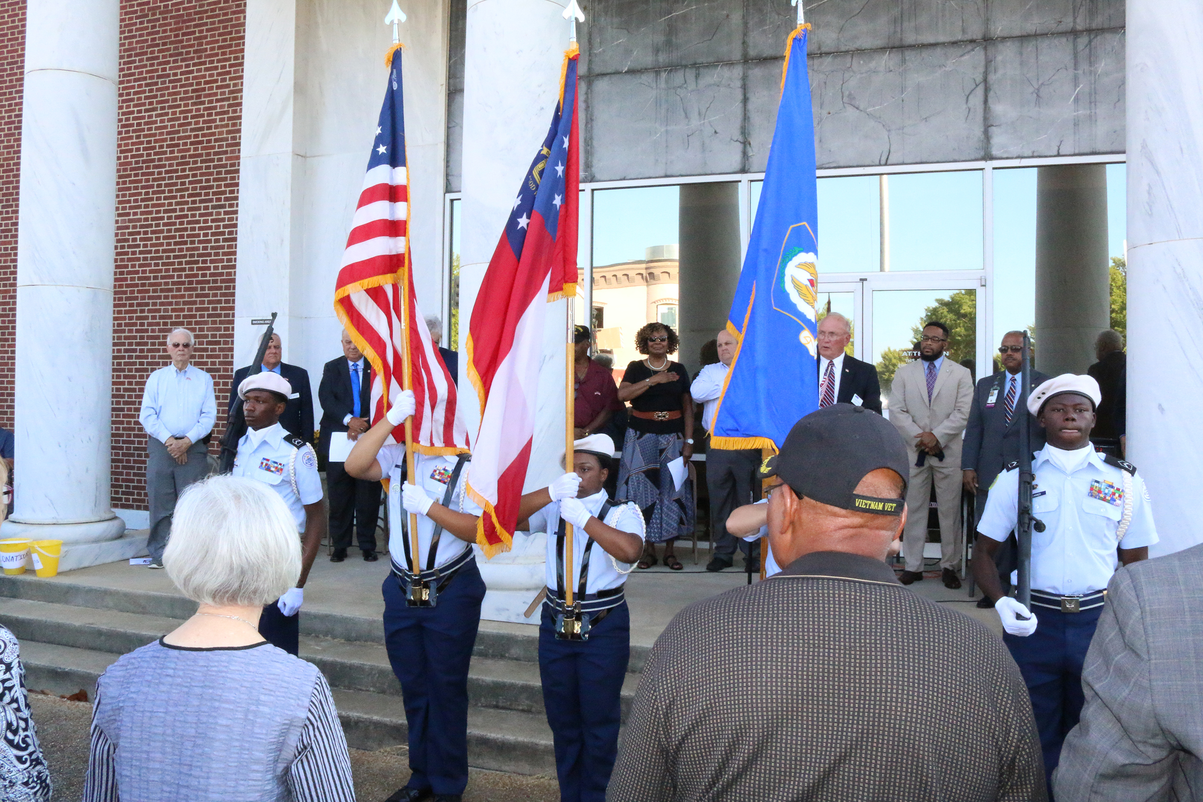 ROTC display the colors at the front steps to the building while a crowd sit in front observing the ceremonies
