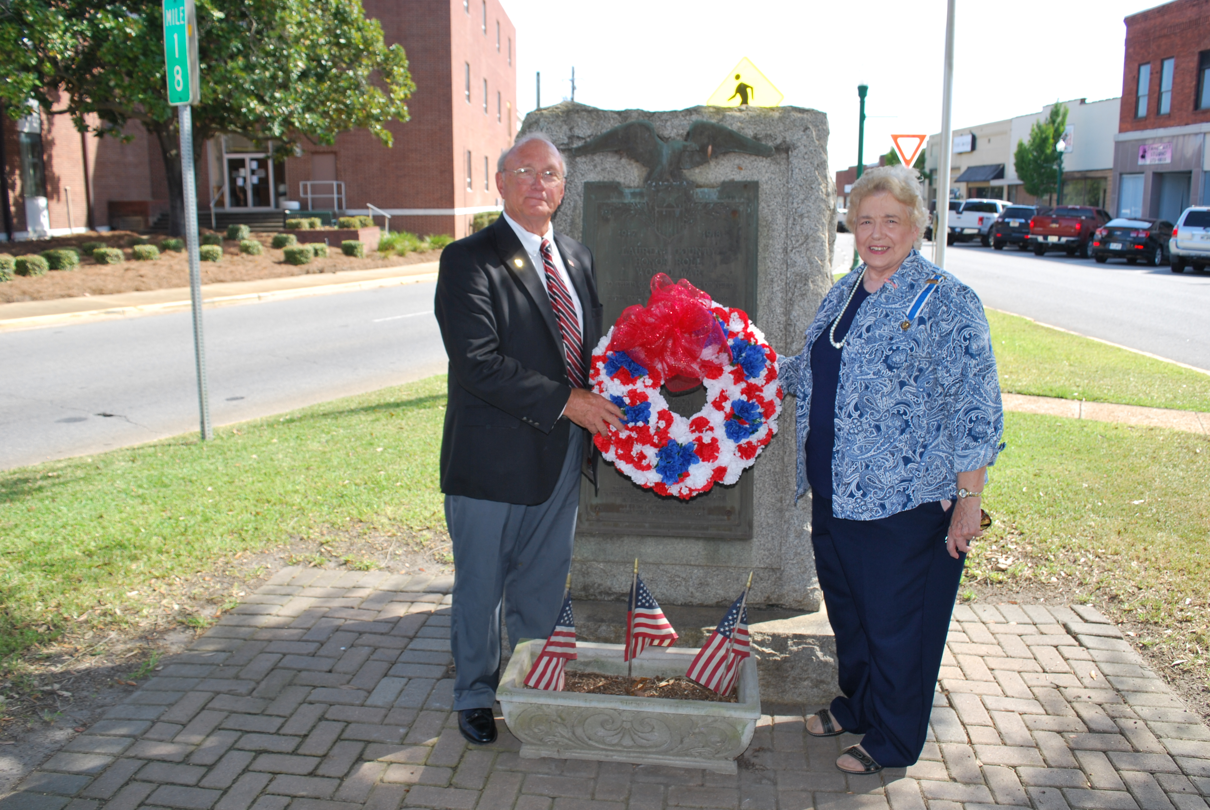 A elderly man and a woman stand in front of the monument holding a red, white, and blue wreath