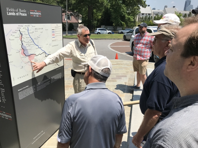 Man talks to a crowd while pointing at a map