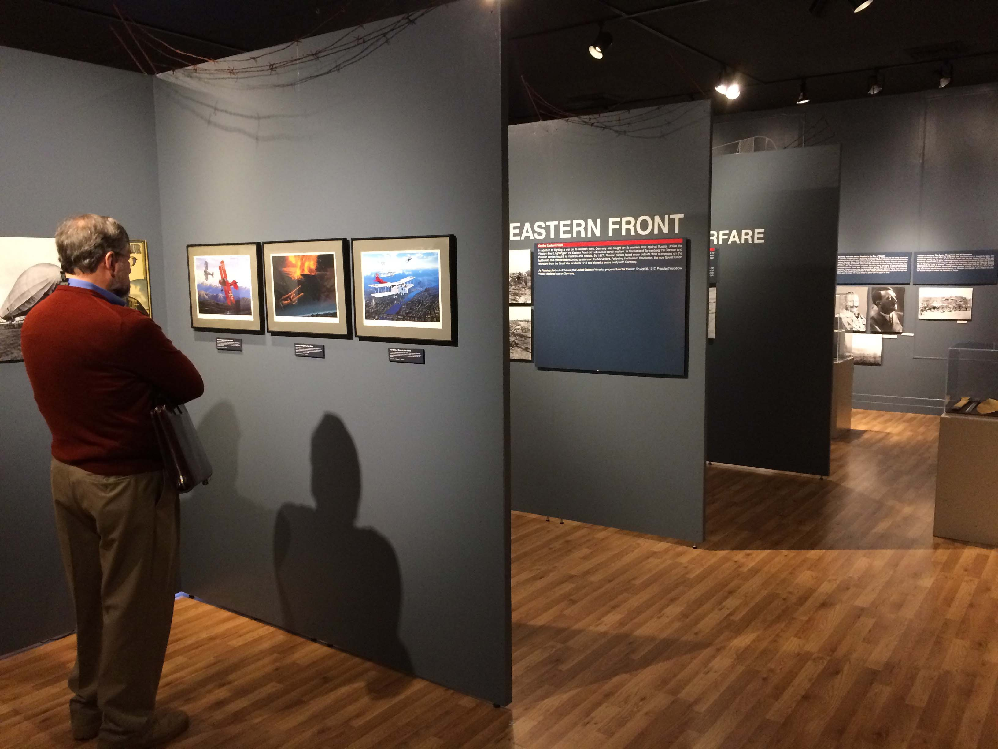 Image of Georgia Southern Museum.  Man standing in front of wall looking at pictures.