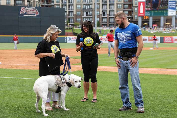 Three people with a service dog on the baseball field.  Left woman holds leash of service dog, center woman has microphone and man on right looks down at service dog