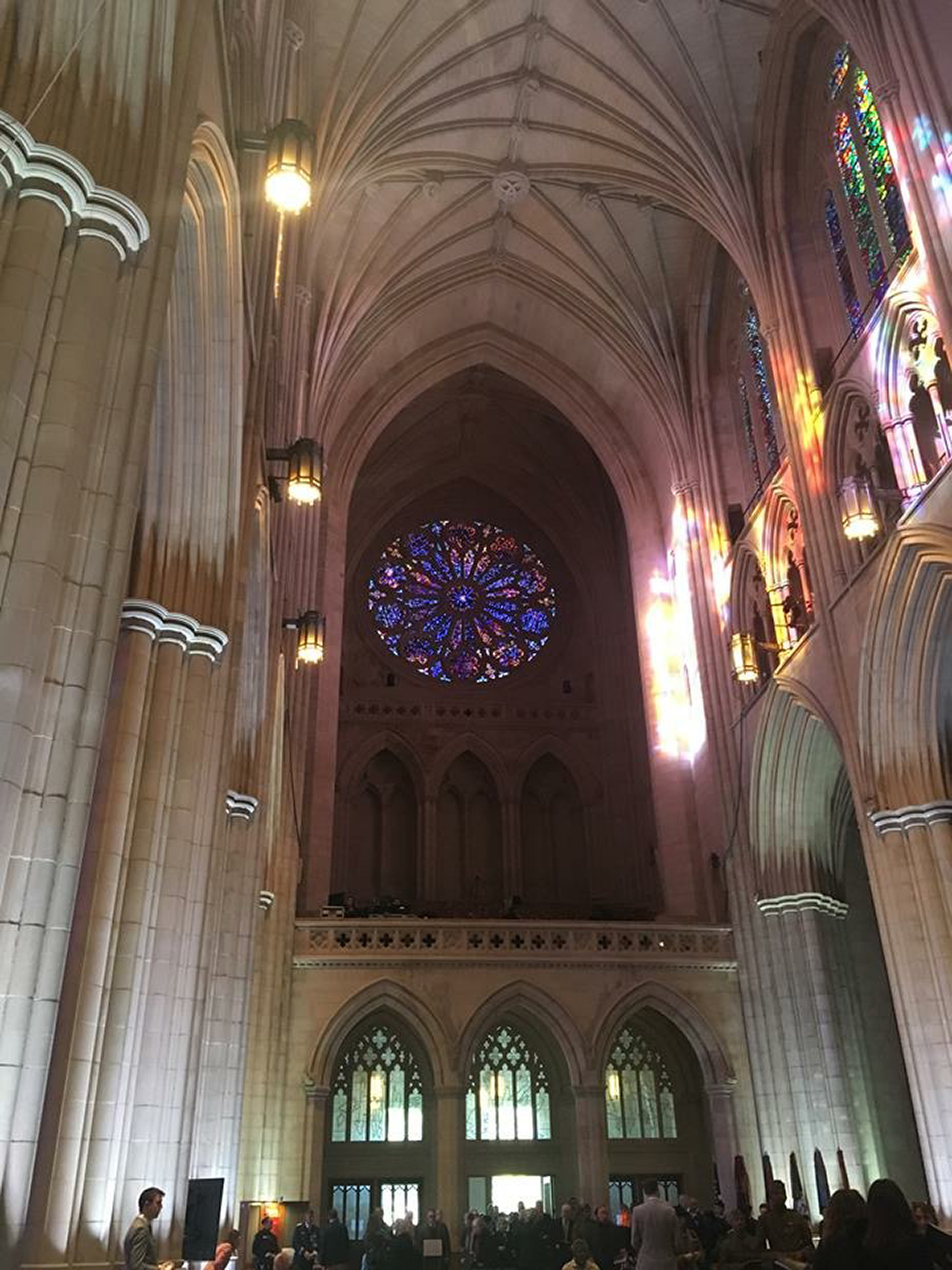 Photo of the inside of the cathedral.  A large, circular stained glass window is the focal point fo the picture