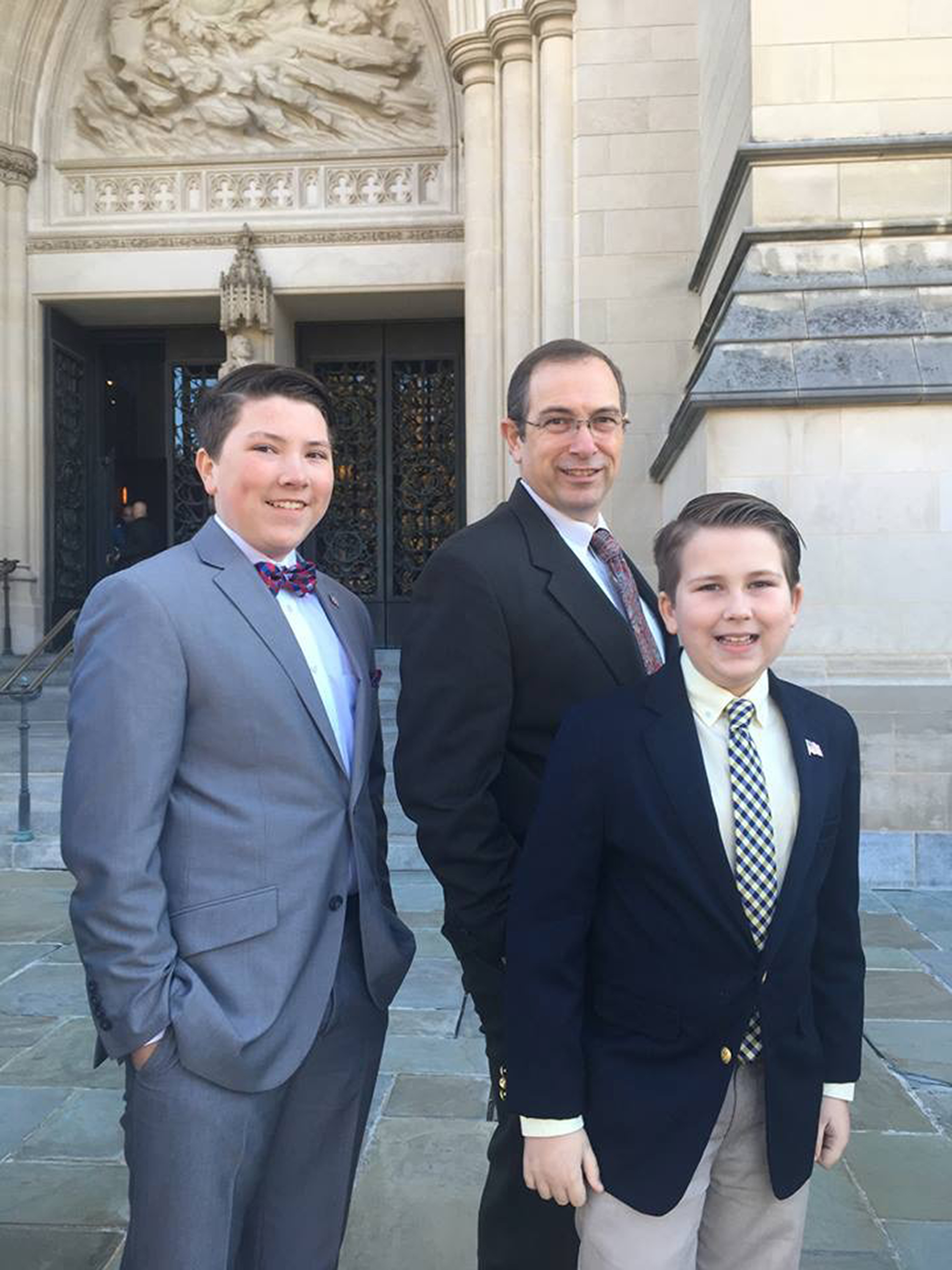 Daniel Wright and his two sons standing outside of the cathedral posing for a picture.
