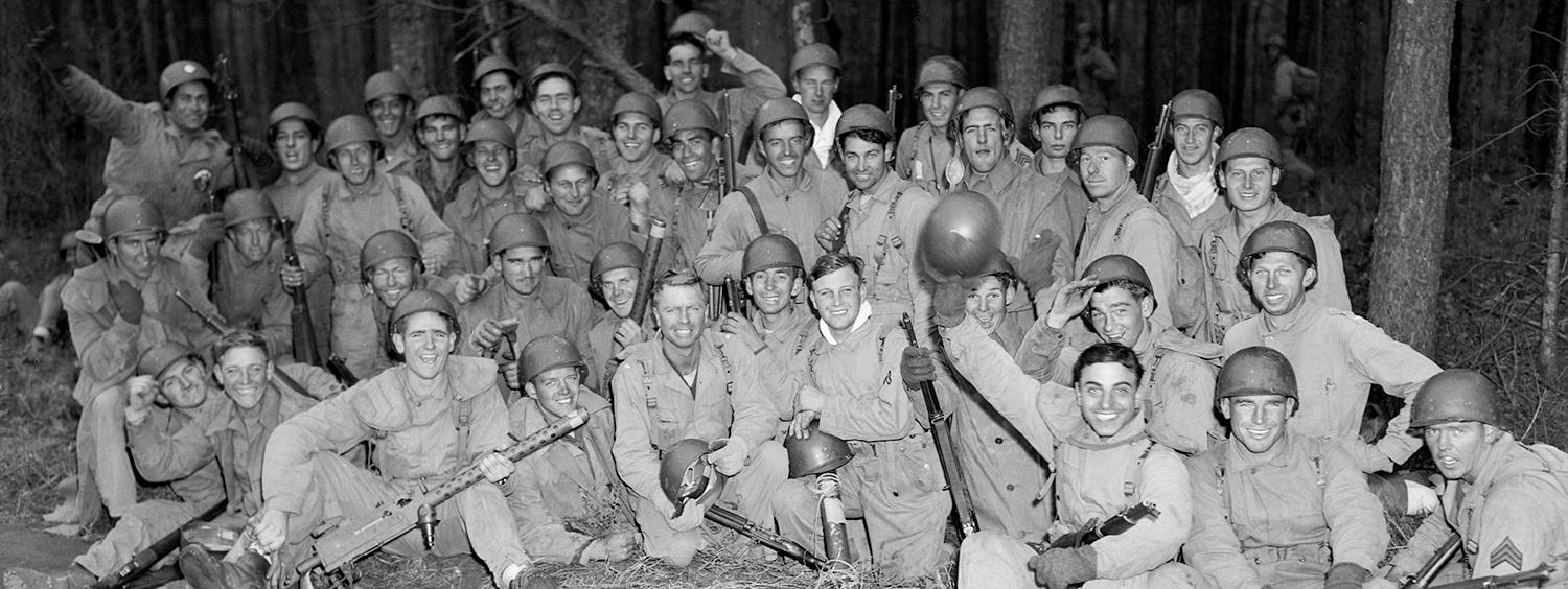 Group of about 50 soldiers sitting on the ground taking a celebratory fun picture