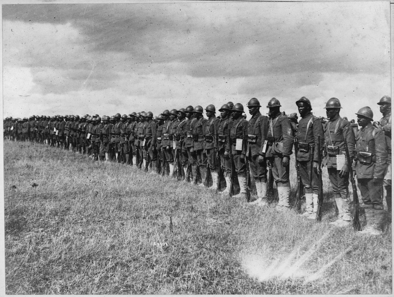 "Troops of the 369th Infantry Regiment (the ""Harlem Hellfighters"") in line. Note their Adrian helmets and Lebel rifles, reflective of their service under French rather than American command owing to contemporary racial attitudes."