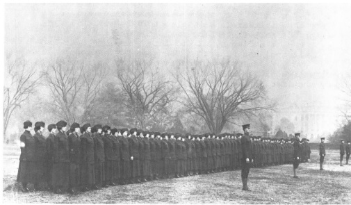 The first women of the Marine Corps Reserve stand at attention before beginning morning drill on the eclipse behind the White House, circa 1918.