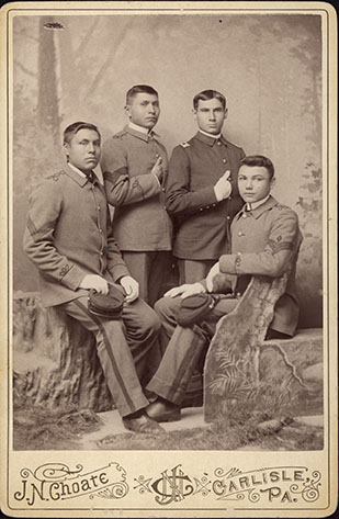 Four male students from Carlisle Indian School wearing military style uniforms, c. 1885.