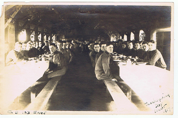 Soldiers sitting around two tables for Thanksgiving Dinner, Camp Hancock, Georgia 1917