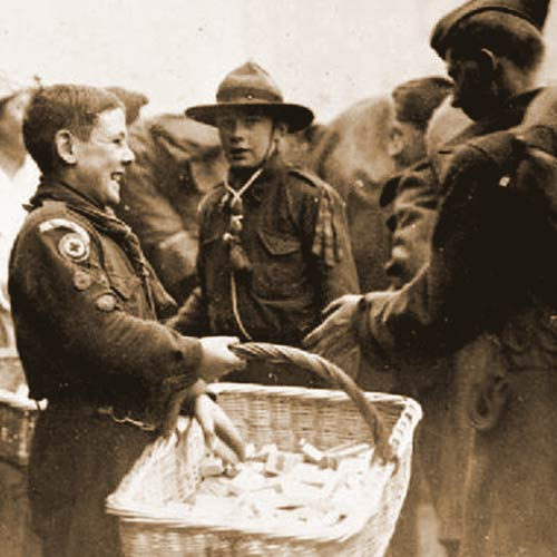 Boy Scouts give out chocolate and cigarettes to departing American troops at Winchester railway station during WWI