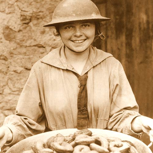 Donut Girl, or Donut Lassie in tin helmet holding a pan of confections